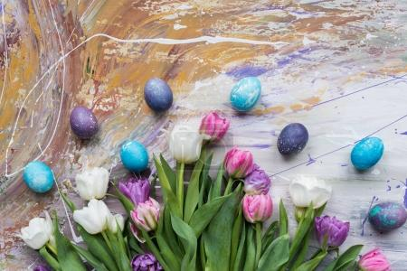Colored eggs and tulips on stained background