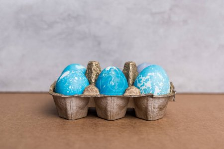 Painted eggs in egg carton on grey background