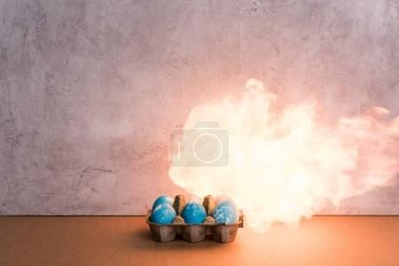 Painted eggs on fire on grey background