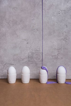 Paint pouring on eggs in cups on grey background