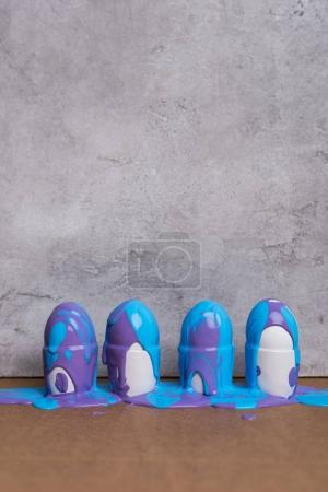 Paint covering eggs in cups on grey background
