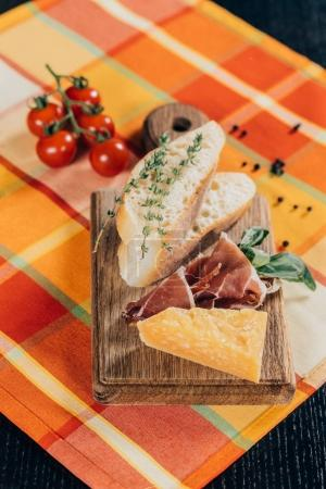 close-up view of sliced baguette, meat and parmesan cheese on wooden cutting board and fresh cherry tomatoes on table