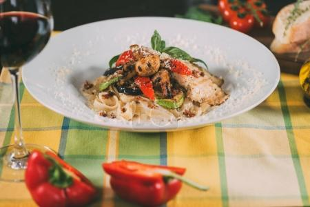 delicious vegetarian pasta with grilled vegetables and parmesan cheese on plate