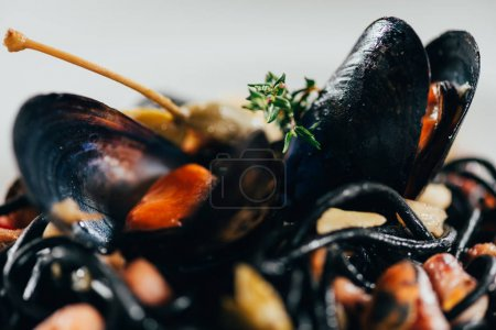 Photo for Close-up view of delicious spaghetti with cuttlefish ink, squid and mussels with octopus - Royalty Free Image