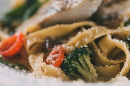 selective focus of gourmet pasta with pike perch fillet, vegetables and parmesan cheese