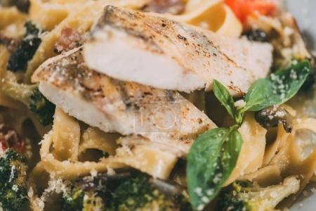 close-up view of delicious pasta with pike perch fillet, vegetables and parmesan cheese