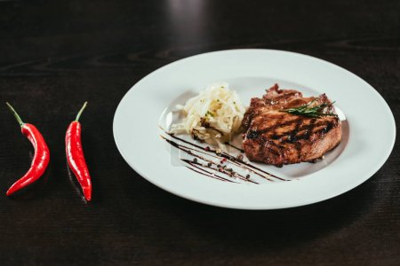 delicious grilled juicy steak with rosemary and chilli peppers on table