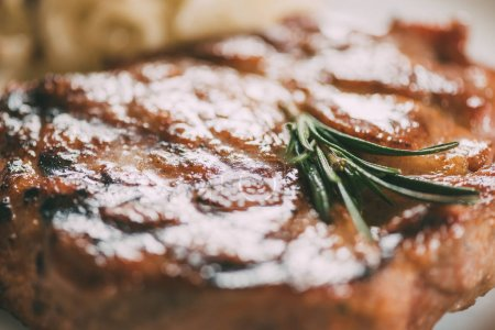 close-up view of fresh hot juicy beef steak with rosemary