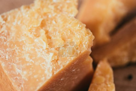 close-up view of delicious parmesan cheese on wooden cutting board
