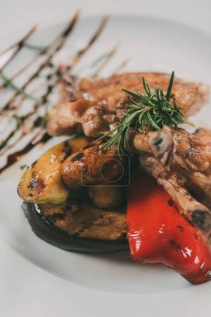close-up view of tasty roasted chicken wings with grilled vegetables on plate