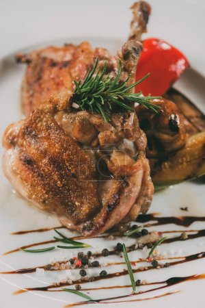 Photo for Close-up view of gourmet roasted chicken with rosemary, spices and sauce on plate - Royalty Free Image