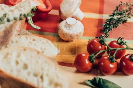 tomates cerises fraîches mûres, champignons et pain tranché sur une serviette de table