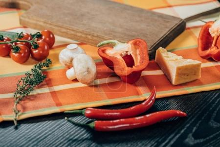 close-up view of fresh ripe vegetables and delicious parmesan cheese on table