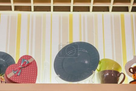 low angle view of decorative plates, cups and heart shaped box in restaurant