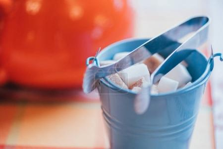 close-up view of small decorative bucket with sugar and tongs on table top