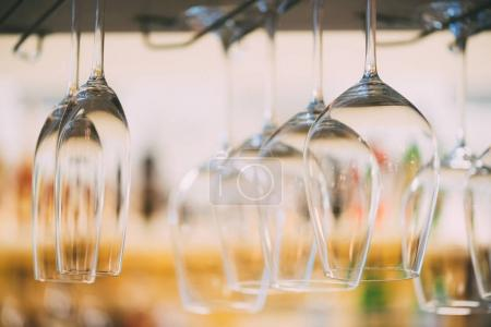 selective focus of clean empty wine glasses hanging in bar counter