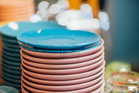 close-up view of stacked clean blue and pink plates in kitchen