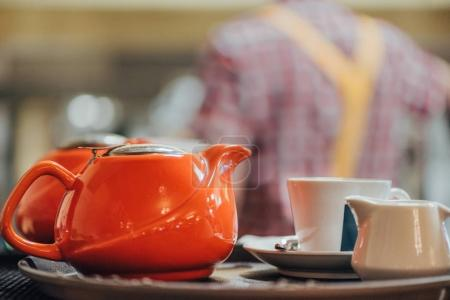 close-up view of red porcelain kettle, cup and white jug on table