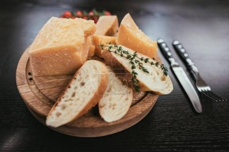 fresh sliced baguette and parmesan cheese on wooden cutting board