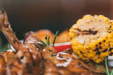 close-up view of delicious roasted chicken with rosemary and corn
