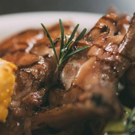 close-up view of delicious grilled chicken with rosemary on plate