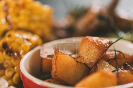 selective focus of tasty grilled corn with roasted potatoes on plate