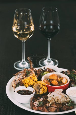glasses of wine and plate with gourmet grilled vegetables and meat on table in restaurant