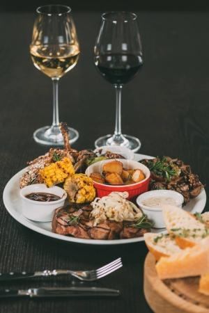 glasses of wine and plate with grilled vegetables and meat on table in restaurant