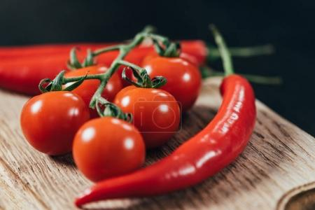 close-up view of fresh ripe cherry tomatoes and chili peppers on wooden cutting board