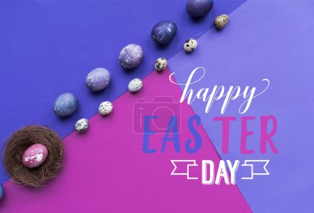 Rows of painted chicken and quail eggs and nest with happy easter day lettering on background in purple tones
