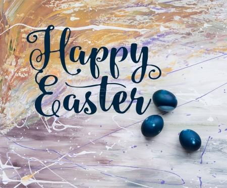 Painted Easter eggs with happy easter lettering on stained background
