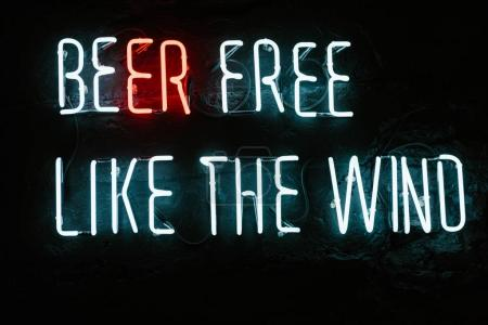 beer free like the wind neon inscription on dark wall in bar