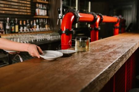 cropped shot of person putting empty plates on wooden bar counter