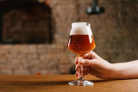 частичный вид лица, держащего стакан свежего холодного пива в пабе