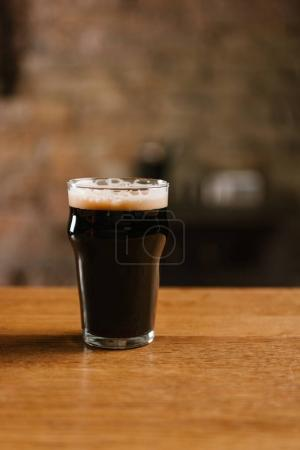 fresh cold dark beer with foam in glass on wooden table in pub