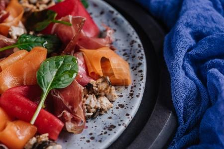 close-up view of fresh gourmet salad with mussels, vegetables and jamon