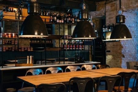 Photo pour Tables en bois, lampes et comptoir de bar dans un restaurant moderne - image libre de droit