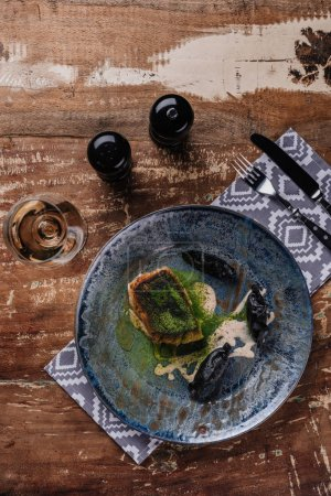top view of delicious fried fish and glass of wine on wooden table