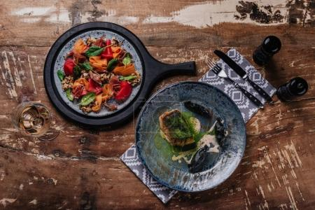 top view of delicious dishes on plates on wooden table