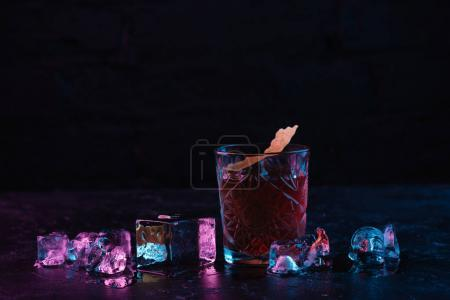 Photo for Close-up view of glass with delicious alcoholic boulevardier cocktail and ice cubes - Royalty Free Image