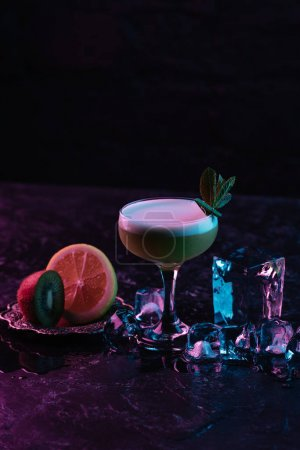 glass of delicious kiwi gin sour cocktail with ice cubes and sliced citrus fruits