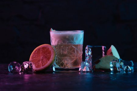 close-up view of glass with ginger nail cocktail and melting ice cubes on dark surface