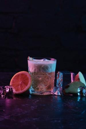 glass with ginger nail cocktail and melting ice cubes on dark surface