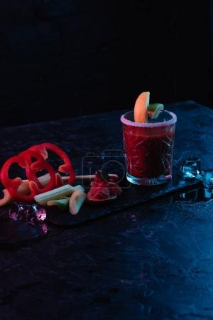 bloody mary cocktail in glass and vegetables with melting ice cubes on dark surface