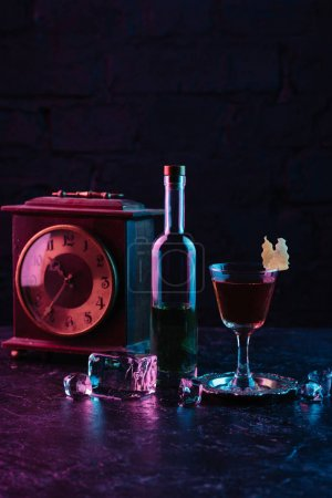 glass of alcohol cocktail, bottle of liquor and vintage clock on dark surface