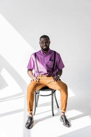 smiling african american man in fashionable clothing sitting on chair on grey backdrop
