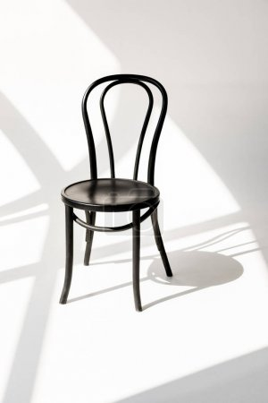close up view of black wooden chair on grey backdrop with shadows