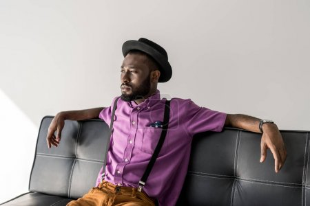 thoughtful african american fashionable man resting on black sofa on grey background