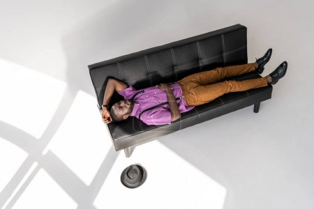high angle view of african american fashionable man lying on black sofa with hat on floor