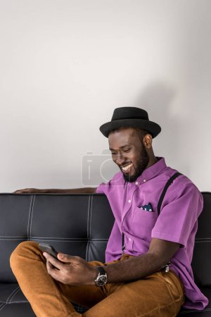 smiling african american stylish man using smartphone on black sofa on grey backdrop